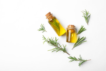 Bottles of rosemary oil and fresh twigs on white background, top view