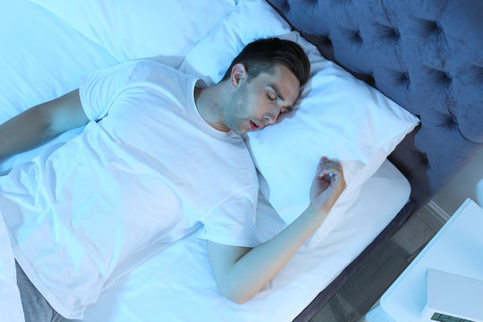 Young man sleeping in bed at night, top view