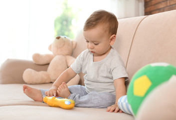 Adorable little baby with toy phone on sofa at home