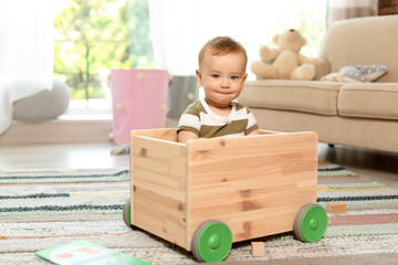 Adorable little baby in wooden cart at home