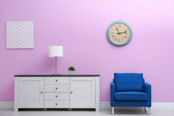 Room interior with stylish clock on wall. Time of day