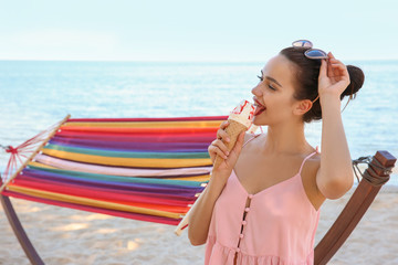 Young woman eating ice cream near hammock at seaside