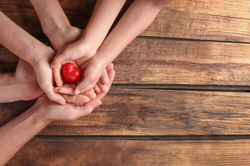 Family holding small red heart in hands on wooden background
