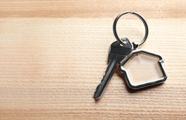 Key with trinket in shape of house on wooden background. Real estate agent services