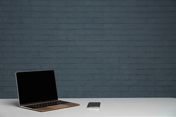 Modern laptop with blank screen and mobile phone on table against brick wall