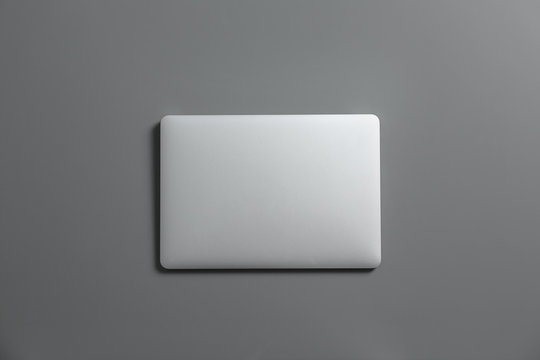 Modern laptop on gray background, top view