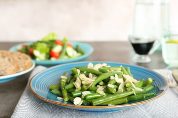 Plate with tasty green beans and almonds on table
