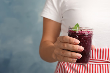 Woman holding mason jar of delicious acai juice, closeup
