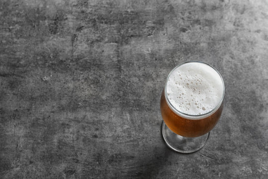 Glass with cold tasty beer on grunge background, view from above