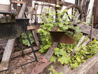 Alte Wagenräder und alte Ackergeräte verrotten auf einem Bauernhof