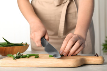Woman cutting raw green beans for tasty dish at table