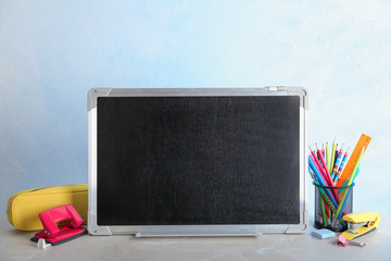 Small chalkboard and different school stationery on table