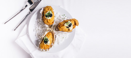 Top view of Deep fried oysters topping with mayonnaise and caviar served in white plate with sea salt decorated.