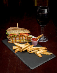 Single glass of red wine with a monster club sandwich with fries