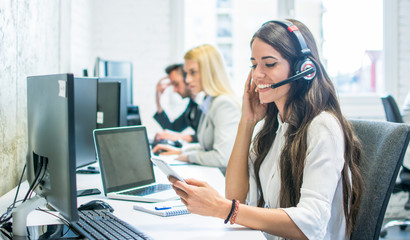 Friendly female customer support operator with headset using phone in office