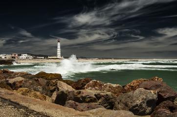 Skaliste wybrzeże, fale rozbijają się o brzeg, w oddali latarnia morska.