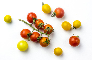 Red and yellow cherry tomatoes on a white background