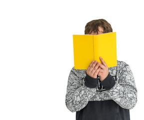 Junge im grauen Pullover liest in einem kleinen gelben Buch, dessen Cover mit einem Text versehen werden kann