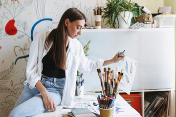 Young thoughtful painter leaning on desk holding paper painting in hand with patterns canvas on background at home