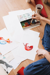 Close up painter sitting on floor drawing by colorful watercolor on paper at home isolated
