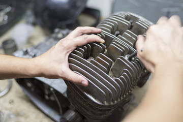 A man fixing a motorcycle motor in a garage, hands holding a cylinder
