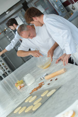 apprentices in pastry learning with experienced chef
