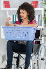 young woman on the wheelchair with laundry basket