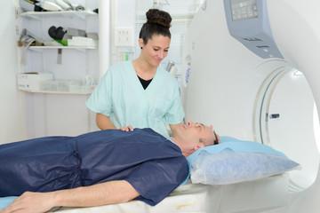 nurse preparing man for ct scan in hospital