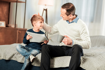 Pleasant communication. Happy joyful man smiling while talking to his son