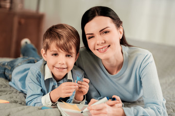 Happy faces. Portrait of positive happy mother and son while smiling to you