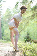 beautiful young chubby girl posing in medieval retro corset and white vintage lingerie in the forest