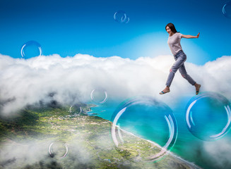 Cute woman jumping in the sky on big soap bubbles