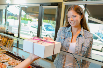 Lady accepting gift wrapped box in a bakery
