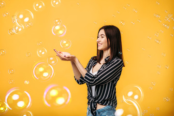 Pretty woman catches soap bubble