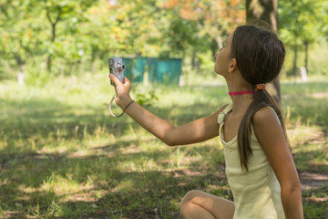 Little cute girl holding camera in hand and take a picture with selfie shot in park. beautiful eight-year-old girl in the park doing selfie