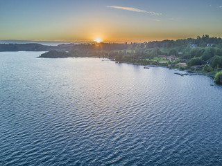 Rupanco Lake, one of the Great lakes in Southern Chile with an amazing aerial view from the drone over Osorno and Puntiagudo Volcanoes surrounded by the water and the trees during the sunset, Chile