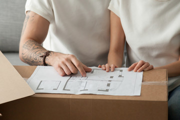 Close up of relocated couple discussing home blueprint on cardboard boxes, considering house remodeling, husband and wife planning apartment interior design, sharing ideas on flat renovation