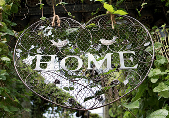 Decorative sign with text Home hangs over the entrance to the garden.