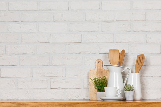 There are various cookers on the table, background made of bricks painted white color only. It feels a homelike atmosphere looking a tidy table in the kitchen.