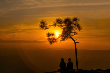 Silhouette couple watching sunset at Lom Sak Cliff, Phukradueng National Park