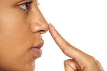 Young dark skinned woman touching her nose