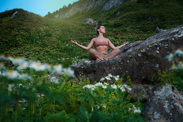 Yoga at park with view of the mountains, with sunlight. Young woman in lotus pose sitting on green grass. Concept of calm and meditation.