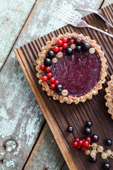 Small vegan tarts made of nuts and berry jam decorated with black, red and white currants on oak cutting board