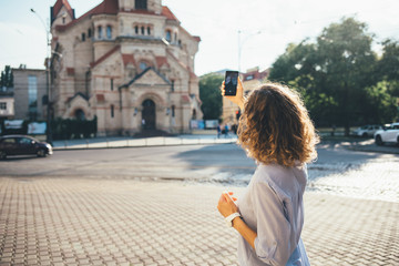 Rear view curly haired young woman traveler photographing architecture