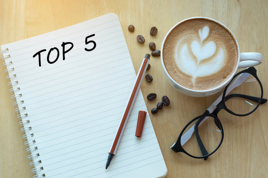 Top 5 word on notebook with glasses, pencil and coffee cup on wooden table. Business, internet, education, technology concept.