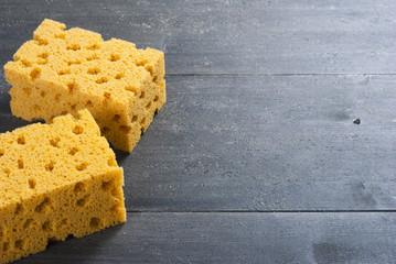 two foam sponges on dark wooden table