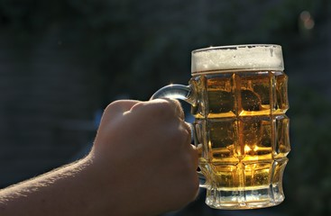 Alcohol,taste and drink concept- closeup man's hand holding a mug of beer on a sunny day.