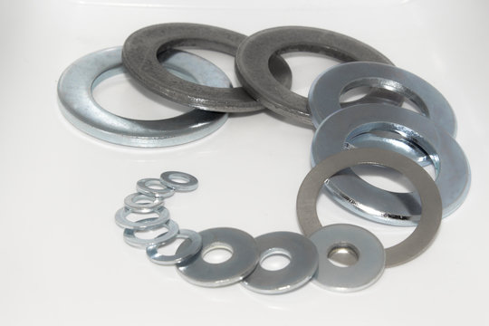 Variety of industrial galvanized steel washers on white background