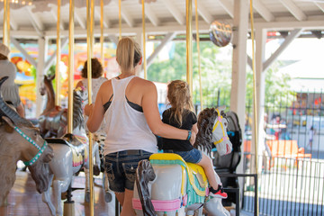 Woman and a child on the carousel in the amusement park