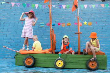 Three happy children boys and funny girl are playing on ship made from old fishing boat. Brothers and sister are happy together on vacation in village. Pirates, sea, adventures, treasures, ocean.